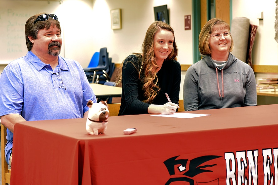 Emily Donovan, daughter of Senior Master Sgt. Rebecca Donovan, 168th Force Development superintendent, Alaska Air National Guard, signs her college letter of intent inside the Ben Eielson High School library, April 27, 2017, Eielson AFB, Alaska. Donovan, sitting between her mom and her dad Mark, will play college volleyball in Tennessee and will study exercise science and sports psychology. (U.S. Air National Guard photo by Senior Master Sgt. Paul Mann/Released)