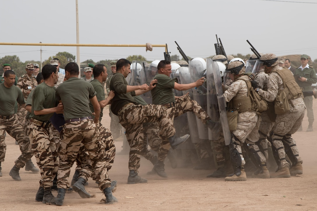 U.S. Soldiers with the 805th Military Police Company, Marines from Marine Company B, 4th Law Enforcement Battalion, and Royal Moroccan Armed Forces defend against rioters during crowd control training at Tifnit, Morocco, on April 24, 2017, during Exercise African Lion. Exercise African Lion is an annually scheduled, combined multilateral exercise designed to improve interoperability and mutual understanding of each nation's tactics, techniques and procedures.