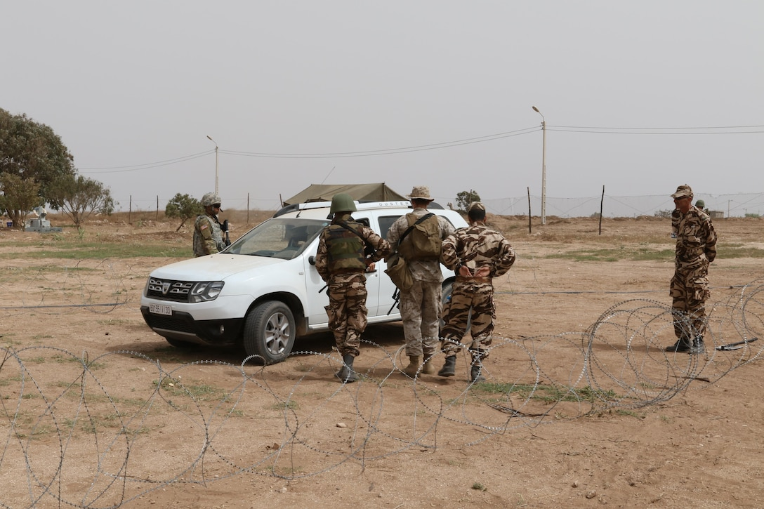 A U.S. Soldier, Marine, and two Moroccan soldiers prepare to search a vehicle in a training vehicle check point in Tifnit, Morocco, on April 22, 2017, during Exercise African Lion. Exercise African Lion is an annually scheduled, combined multilateral exercise designed to improve interoperability and mutual understanding of each nation's tactics, techniques and procedures.