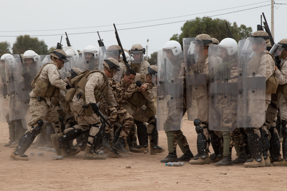 Marines with Marine Company B, 4th Law Enforcement Battalion, Soldiers with the 805th Military Police Company, and Royal Moroccan Armed Forces subdue the leader of the pseudo-rioters as part of crowd control training during Exercise African Lion in Tifnit, Morocco, on April 24, 2017. Exercise African Lion is an annually scheduled, combined multilateral exercise designed to improve interoperability and mutual understanding of each nation's tactics, techniques and procedures.