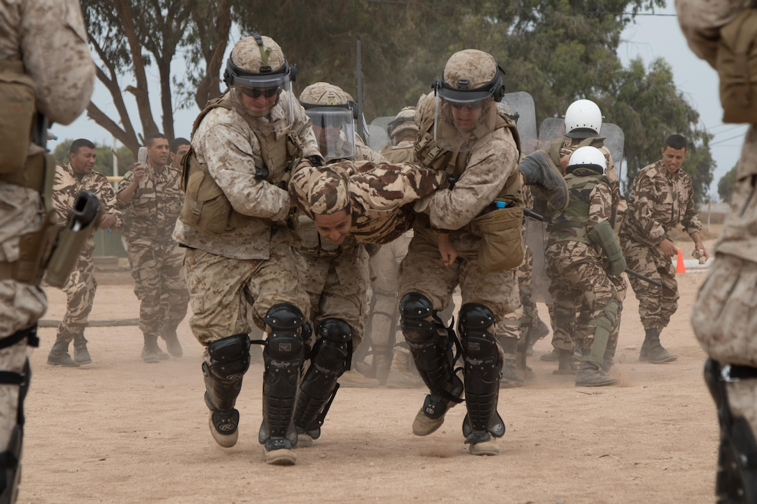 U.S. Soldiers with the 805th Military Police Company, Marines from Marine Company B, 4th Law Enforcement Battalion, and Royal Moroccan Armed Forces carry a rioter behind friendly lines during crowd control training at Tifnit, Morocco, on April 24, 2017, during Exercise African Lion. Exercise African Lion is an annually scheduled, combined multilateral exercise designed to improve interoperability and mutual understanding of each nation's tactics, techniques and procedures.