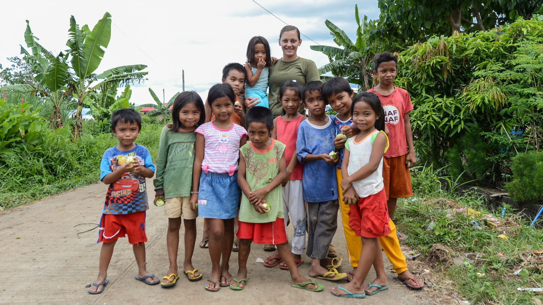 U.S. Marine Lance Cpl. Brook Klahn with 9th Engineer Support Battalion poses for a group photo with the local kids during Balikatan 2017 in Ormoc City, Leyte, April 24, 2017.