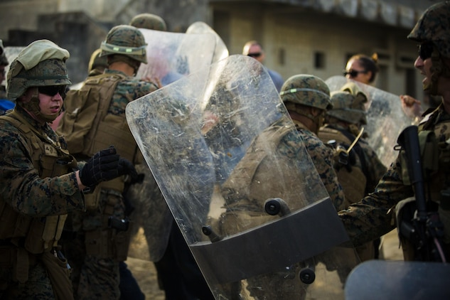 Marines defend against role players at Central Training Area, Camp Hansen, Okinawa, Japan, April 19, 2017. 3d Law Enforcement battalion conducted a Marine Corps Combat Readiness Evaluation to test each company's ability to execute tasks ranging from policing operations to police patrolling, route regulations, key leader engagements in towns and local population centers, security of key infrastructure, identity operations and law enforcement operations in an expeditionary environment to ensure they are prepared to support the operational requirements of III Marine Expeditionary Force. The Marines are with Charlie Company, 3d LE Bn, III MEF Headquarters Group. (U.S. Marine Corps photo by Lance Cpl. Joshua Pinkney)