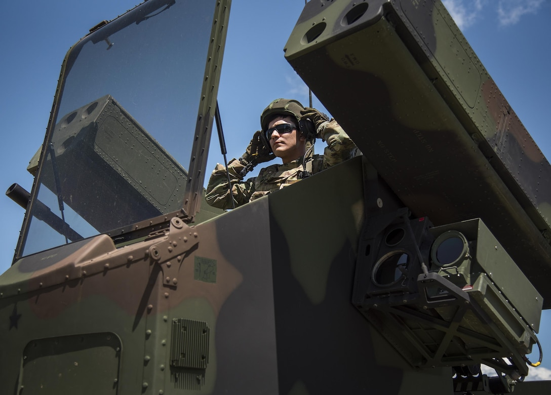 Spc. Christopher Bazan, Florida National Guard 3rd Battalion, 265 Air Defense Artillery Regiment, puts on his helmet before closing the canopy on the Avenger's turret April 20.  The unit along with the Army's Stinger Based Systems used the Eglin Air Force Base range to test fire stinger missiles from the vehicle. (U.S. Air Force photo/Samuel King Jr.)