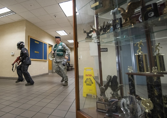 A simulated gunman searches for targets at the beginning of an active shooter exercise at Eglin Air Force Base, Fla., April 11.  The goal of the exercise was to evaluate people's knowledge and response at the active shooter location and select lockdown locations.  (U.S. Air Force photo/Samuel King Jr.)