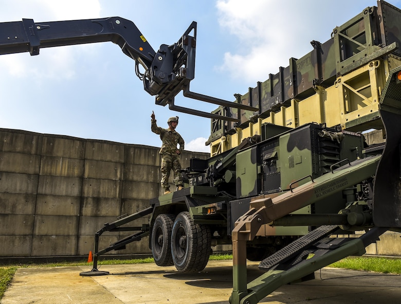 U.S. Army Spc. Justin Maurer Alpha Battery, 2nd Battalion, 1st Air Defense Artillery Regiment patriot missile operator and maintainer, guides a fork lift while maneuvering dummy munitions on a patriot missile system at Kunsan Air Base, Republic of Korea, July 27, 2017. Maurer took part in a week-long field training exercise that included proper 24-hour manning and changeover for crew operations, Patriot Launcher reloads, and Operational Readiness Evaluations. (U.S. Air Force photo by Senior Airman Michael Hunsaker/Released).