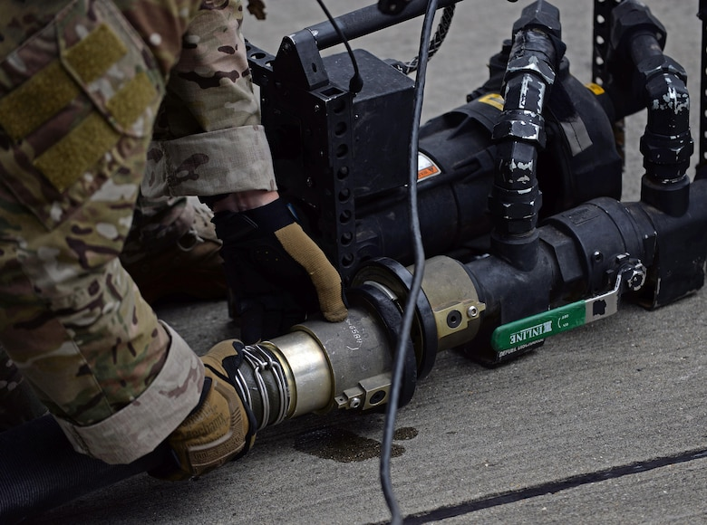 A U.S. Air Force 67th Special Operations Squadron loadmaster hooks up a fuel hose running from an MC-130J Commando II to a pump July 26, 2017, on RAF Mildenhall, England. The pump is used to assist with pumping any residual fuel from the hose back into the MC-130J. (U.S. Air Force photo by Airman 1st Class Luke Milano)