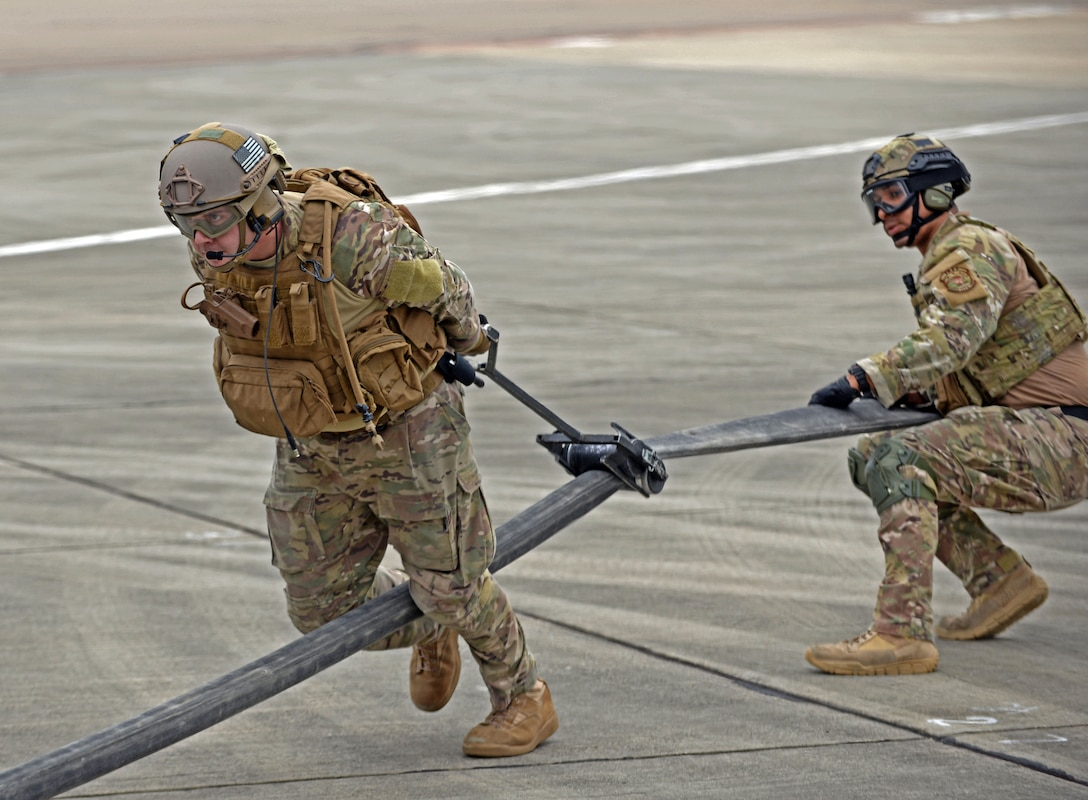 U.S. Air Force Airman 1st Class Michael Ricci, right, 100th Logistics Readiness Squadron Forward Arming and Refueling Point  technician aids a U.S. Air Force 67th Special Operations Squadron loadmaster with removing residual fuel from a hose using a tool called a 'squeegee' July 26, 2017, on RAF Mildenhall, England. During the Forward Arming and Refueling Point exercise, approximately 27,000 pounds of fuel was transferred from an MC-130J to four F-15Cs. (U.S. Air Force photo by Airman 1st Class Luke Milano)