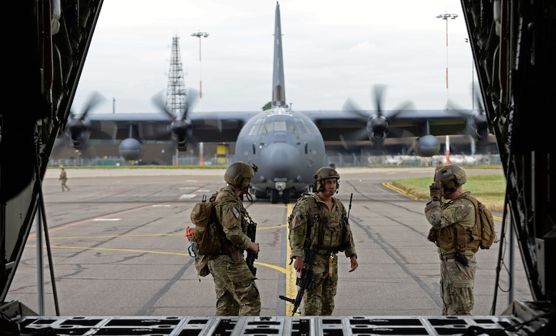 Two U.S. Air Force 352d Special Operations Squadron Deployed Aircraft Ground Response Element team members assist with airfield security while a 67th Special Operations Squadron loadmaster finishes unloading F-15C Eagle, from RAF Lakenheath weapons crews and supplies from an MC-130J Commando II during a Forward Arming and Refueling Point, or FARP, exercise July 26, 2017, on RAF Mildenhall, England.  The FARP exercise included two MC-130Js along with four F-15Cs. (U.S. Air Force photo by Airman 1st Class Luke Milano)