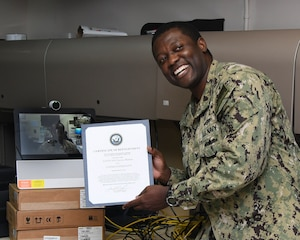 MANAMA, Bahrain (July 27, 2017) Information Systems Technician 2nd Class Lucian Matthias, assigned to U.S. Naval Forces Central Command, poses for a photo after having been administered the oath of enlistment by his brother Army Maj. Leon H. Matthias Jr., assigned to 532nd Military Intelligence Battalion, 501st Military Intelligence Brigade in Camp Humphreys, South Korea, on screen, via a video teleconference. (U.S. Navy photo by Mass Communication Specialist 2nd Class Victoria Kinney)
