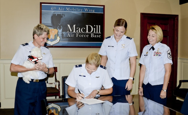 U.S. Air Force Col. April Vogel, center, commander of the 6th Air Mobility Wing, signs the Paw Support Program proclamation at MacDill Air Force Base, Fla., July 31, 2017. The Paw Support Program uses animal therapy to help sexual assault victims cope with the trauma they have experienced. (U.S. Air Force photo by Staff Sgt. Brittany Liddon)