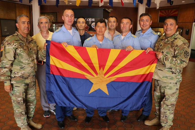 Command Sgt. Major Fidel Zamora, the senior enlisted advisor for the Arizona Army National Guard and Command Sgt. Major Saul Garcia, the command sergeant major for the 98th Aviation Troop Command, hold the Arizona state flag with delegates from Kazakhstan during a visit to exchange aviation maintenance practices and non-commissioned officer development July 25. The visit came within weeks of the U.S. government's formal renewal of its partnership with Kazakhstan, extending the 24-year-old legacy of cooperation for five more years. (Ariz. Army National Guard photo by Maj. Kevin Budak)