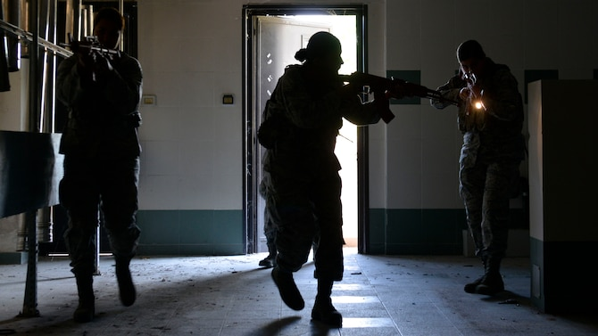 Airmen from the 31st Security Forces Squadron perform a security check in a room during close-quarters battle training, July 27, 2017, at Aviano Air Base, Italy. Approximately 50 defenders practiced clearing unoccupied buildings on base during simulated training scenarios involving hostage situations. (U.S. Air Force photo by Senior Airman Cary Smith)
