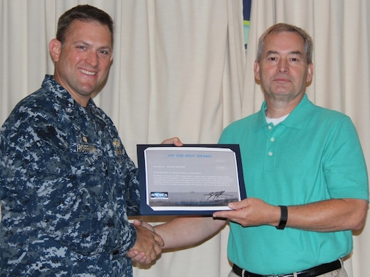 CDSA Dam Neck Commanding Officer Cmdr. Andrew J. Hoffman presents a $50 on-the-spot award to Mr. Roger Messer of CDSA's Information Management branch for his contributions to High Velocity Learning at the command.