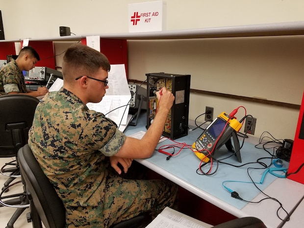 PFC Tance Brandon is seen here troubleshooting a NIDA radio trainer during the Amplitude Modulation (AM) annex of the Ground Radio Repair Course. This trainer provides an introduction to radio fundamentals and allows for hands-on troubleshooting. This training, as well as the later training Marines receive in the course, allows for understanding of how radio assets operate. This prepares the Marines for their future responsibilities as Military Occupational Specialty 2841, Ground Radio Repairers.
