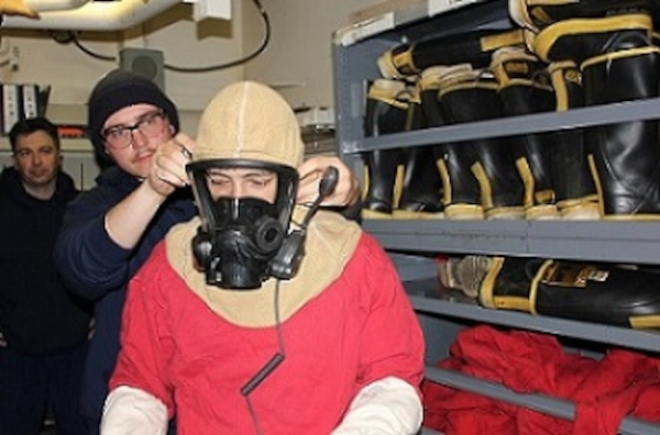 SN Weesner assists SA Rife in donning an SCBA mask.