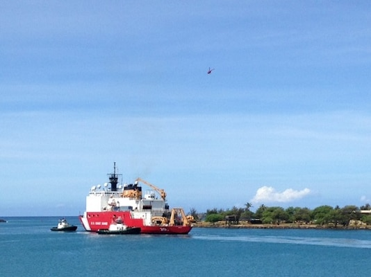 USCGC HEALY departs Honolulu, flanked by two tug boats.