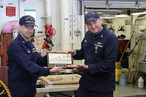 CDR Karl Lander, USCG, Ret. receives the coveted HEALY plaque, from CAPT Jason Hamilton.