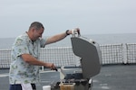 F&S2 Sterling Van Horn prepares burgers on the flight deck for the morale meal.