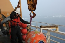 BM2 Jim Bowell prepares the mooring ball for redeployment.