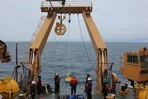 The Deck Department observes gear deployed from the aft a-frame.