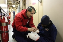 MK1 Nicholas Mersch practices administering first aid on SK2 Ronald Milton.