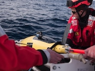 HEALY's small boat recovers one of the two Wave Gliders.