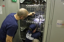 EM1 Espinosa and EMCM Hudson replacing a cycloconverter circuit card.