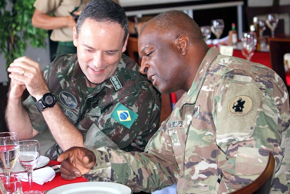 Col. Fabiano Lima de Carvalho, from Brazil Army Plans and Col. Tim Phillips, director of Army South logistics, talk during lunch July 24.