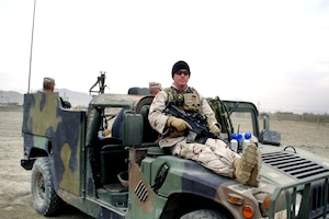 Then-Staff Sgt. Tom Farrington sits on the hood of a Humvee during a halt on a mission while deployed to Iraq in 2004 with the Indiana Army National Guard's D Company (Long Range Surveillance), 1st Battalion, 151st Infantry Regiment.