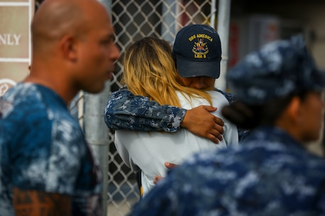A sailor stationed aboard the USS America LHD-6 embraces his spouse before boarding the ship at Naval Base San Diego prior to departing on the America Amphibious Ready Group/15th Marine Expeditionary Unit's Western Pacific 17-2 deployment July 7, 2017. The 15th MEU will provide a forward-deployed, flexible sea-based Marine Air-Ground Task Force capable of conducting a variety of combat and humanitarian missions. (U.S. Marine Corps photo by Sgt. Will Perkins)