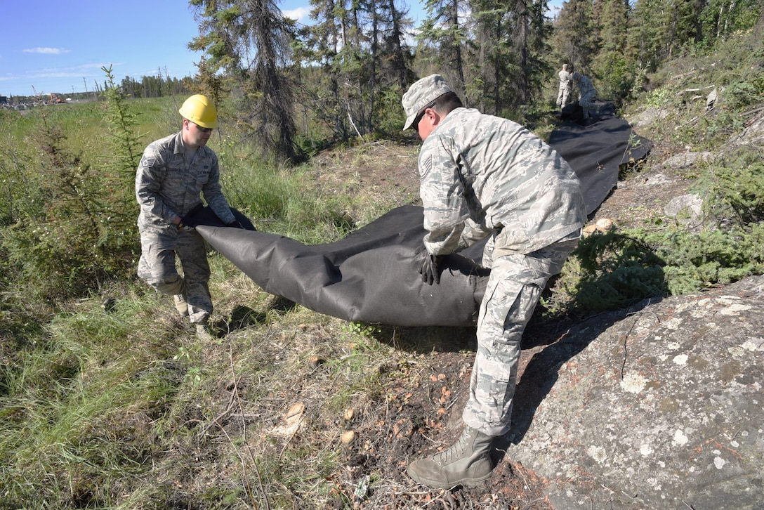 Oregon Air National Guard Staff Sgt. Daniel Hagemier, assigned to the 142nd Fighter Wing Civil Engineers Squadron (left), and Tech. Sgt. Charles Jedda (right), move a large role of stabling material to provide a base for rock and other materials, extending a public trail at Niven Lake at Yellowknife, Northwest Territories, Canada, July 18, 2017. The Civil Engineer Airmen are spending two-weeks in Canada working with Canadian Armed Forces members from Cold Lake, Alberta, Canada, on a variety of projects during their Deployment for Training (DFT). (U.S. Air National Guard photo/Master Sgt. John Hughel, 142nd Fighter Wing Public Affairs)