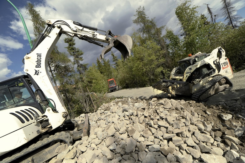 Oregon Air National Guard Chief Master Sgt. Ronald Eckert (left), 142nd Fighter Wing Civil Engineers (CES), operates a excavator to load rock and other materials used to build a new trail at Niven Lake, Yellowknife, Northern Territories, Canada, July 18, 2017. Over 30 CES members are spending two-weeks in Canada working on a variety of projects during their Deployment for Training (DFT). (U.S. Air National Guard photo/Master Sgt. John Hughel, 142nd Fighter Wing Public Affairs)