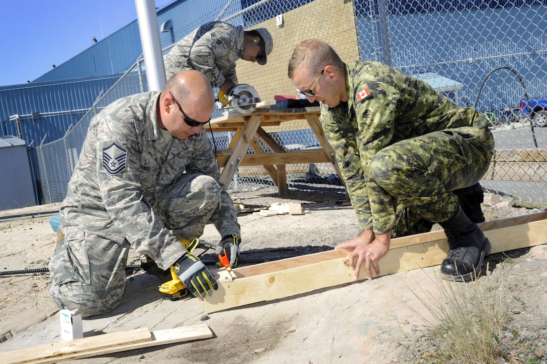Oregon Air National Guard Master Sgt. Travis McDaniel, (left) assigned to the 142nd Fighter Wing Civil Engineer Squadron (CES) and Canadian Armed Forces Lt. Jordan Vadala (right) construct concrete form to install a new lighting project at the 440th Squadron/Escadrille, Yellowknife, Northwest Territories, Canada, July 19, 2017. (U.S. Air National Guard photo/Master Sgt. John Hughel, 142nd Fighter Wing Public Affairs)