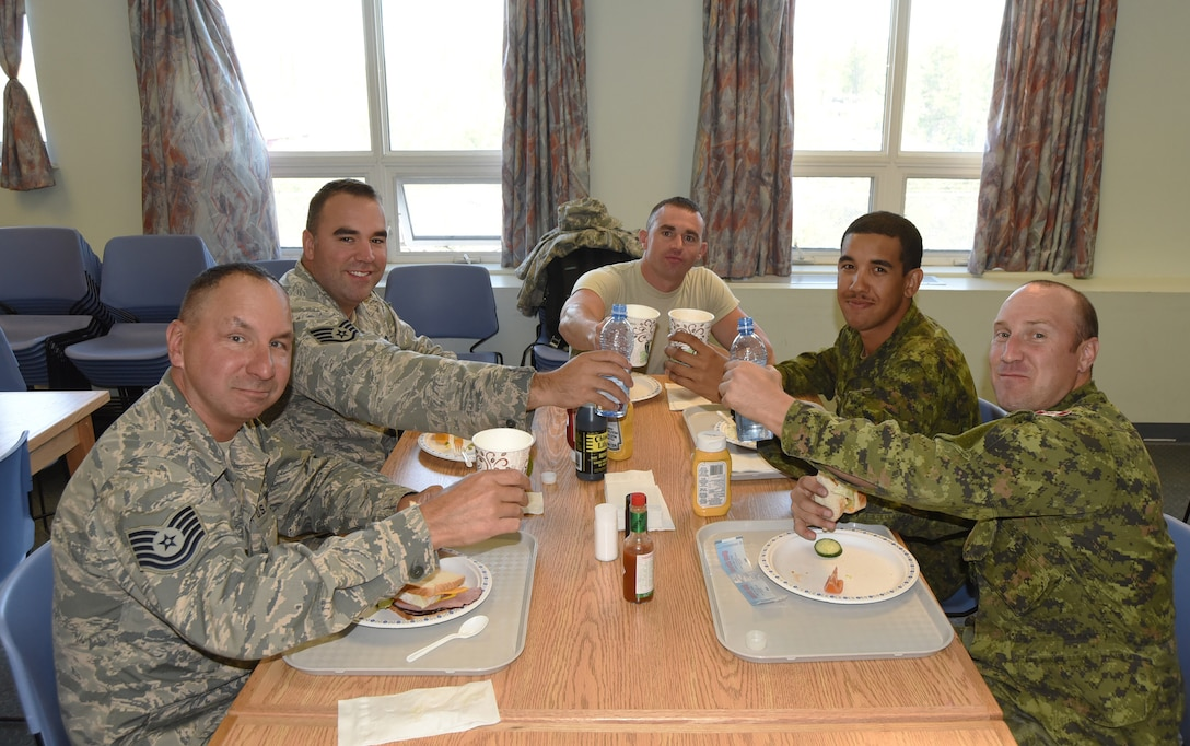 Oregon Air National Guard members along with Canadian Military members from Cold Lake, Alberta, enjoy lunch together during their joint Deployment for Training (DFT) in Yellowknife, Northwest Territories, Canada, July 20, 2017. The Civil Engineer Airmen are spending two-weeks in Canada working with Canadian Armed Forces members from Cold Lake, Alberta, Canada, on a variety of projects during their DFT. (Picured from left to right) Tech. Sgt. David Sherman, Staff Sgt. Tyler O'Bryant, Staff Sgt. Michael Templeton, Private Corey Blackmore and Corporal Kyle Burrow. (U.S. Air National Guard photo/Master Sgt. John Hughel, 142nd Fighter Wing Public Affairs)