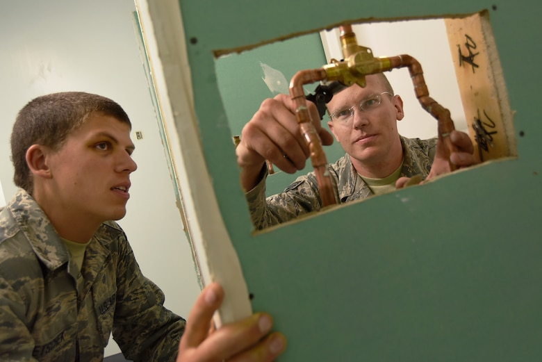 Oregon Air National Guard Staff Sgt. Benjamin Schultz (right), makes adjustments to newly installed plumbing fixtures, while Airman 1st Class Joshua Bietschek (left), observes the procedures as part of his ongoing training, as the two members assigned to the 142nd Civil Engineer Squadron work on a variety of construction and repair projects during their Deployment For Training (DFT) in Yellowknife, Northwest Territories, Canada, July 21, 2017. The Oregon Airmen are also collaborating with Canadian Armed Forces members from Cold Lake, Alberta, who are also deployed to Yellowknife for training. (U.S. Air National Guard photo/Master Sgt. John Hughel, 142nd Fighter Wing Public Affairs)