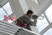 Oregon Air National Guard Christoper Black, assigned to the 142nd Fighter Wing Civil Engineer Squadron (CES) works to install new lights at the Joint Task Force North (JTFN) Headquarters building, Yellowknife, Northwest Territories, Canada, July 21, 2017. The Oregon CES members are deployed for two-weeks for training along with CAF members from Cold Lake, Alberta. (U.S. Air National Guard photo/Master Sgt. John Hughel, 142nd Fighter Wing Public Affairs)