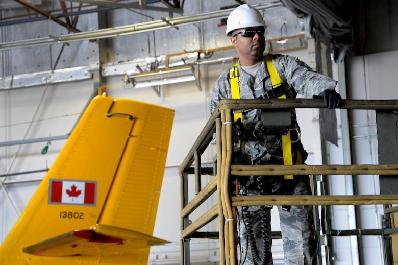 Oregon Air National Guard Staff Sgt. Brandon Bingham, assigned to the 142nd Fighter Wing Civil Engineer Squadron (CES) moves a scissor lift into place to install new lights for the 440th Squadron/Escadrille hangar, Yellowknife, Northwest Territories, Canada, July 21, 2017. The Oregon CES members are deployed for two-weeks for training along with CAF members from Cold Lake, Alberta. (U.S. Air National Guard photo/Master Sgt. John Hughel, 142nd Fighter Wing Public Affairs)