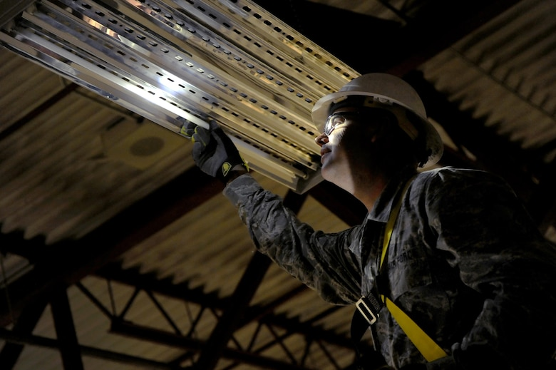 Oregon Air National Guard Master Sgt. Travis McDaniel, assigned to the 142nd Fighter Wing Civil Engineer Squadron (CES) inspects a hangar light fixture for replacement at the 440th Squadron/Escadrille, Yellowknife, Northwest Territories, Canada, July 21, 2017. Over 30 CES members are spending two-weeks in Canada working on a variety of projects during their Deployment for Training (DFT). (U.S. Air National Guard photo/Master Sgt. John Hughel, 142nd Fighter Wing Public Affairs)