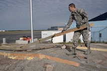 Oregon Air National Guard Staff Sgt. Christopher Walley, assigned to the 142nd Fighter Wing Civil Engineer Squadron (CES) removes wooden concrete forms as part of a lighting project at the 440th Squadron/Escadrille, Yellowknife, Northwest Territories, Canada, July 24, 2017. (U.S. Air National Guard photo/Master Sgt. John Hughel, 142nd Fighter Wing Public Affairs)