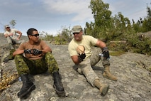 Oregon Air National Guard Staff Sgt. Tyler O;Bryant (right), assigned to the 142nd Fighter Wing Civil Engineer Squadron, discusses a tree core sample with Canadian Armed Forces Private Corey Blackmore (left) during a rest break while clearing trees at Niven Lake, Yellowknife, Northwest Territories, Canada, July 24, 2017. The Oregon Airmen are also collaborating with Canadian Armed Forces members from Cold Lake, Alberta, who are also deployed to Yellowknife for training. (U.S. Air National Guard photo/Master Sgt. John Hughel, 142nd Fighter Wing Public Affairs)