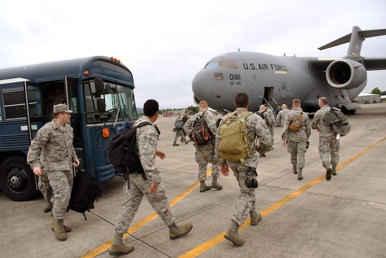 Airmen from the 142nd Fighter Wing depart busses and begin to load a waiting C-17 Globemaster III at the Portland Air National Guard Base, Ore., that will transport them to Nellis Air Force Base, Nev., and support the Weapons Instructor Course, May 29, 2017 (U.S. Air National Guard photo by Master Sgt. John Hughel, 142nd Fighter Wing Public Affairs).