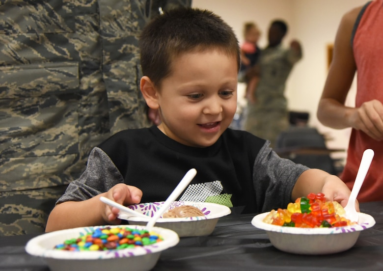 Everett Garcia, son of 2nd Lt. Anthony Garcia, 81st Security Forces Squadron operations officer, reaches for gummy bears during a family ice cream social at the 81st SFS building July 27, 2017, on Keesler Air Force Base, Miss. The event, hosted by the 81st SFS Defenders Council and Key Spouses, also consisted of a military working dog demonstration and a combat arms weapons display. (U.S. Air Force photo by Kemberly Groue)
