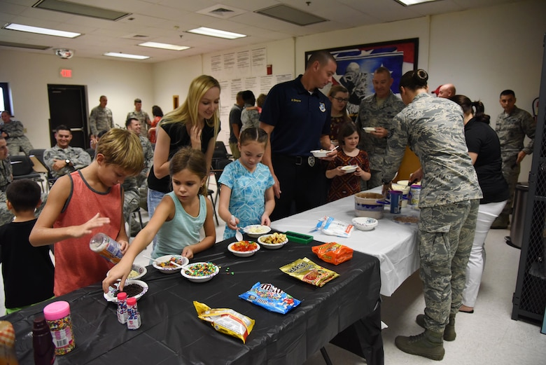 Personnel and family members from the 81st Security Forces Squadron make a bowl of ice cream during a family ice cream social at the 81st SFS building July 27, 2017, on Keesler Air Force Base, Miss. The event, hosted by the 81st SFS Defenders Council and Key Spouses, also consisted of a military working dog demonstration and a combat arms weapons display. (U.S. Air Force photo by Kemberly Groue)