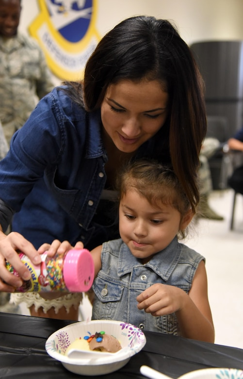 Priscilla and Rosalie Murray, family members of Maj. Jonathon Murray, 81st Security Forces Squadron commander, sprinkle candy on their ice cream during a family ice cream social at the 81st SFS building July 27, 2017, on Keesler Air Force Base, Miss. The event, hosted by the 81st SFS Defenders Council and Key Spouses, also consisted of a military working dog demonstration and a combat arms weapons display. (U.S. Air Force photo by Kemberly Groue)