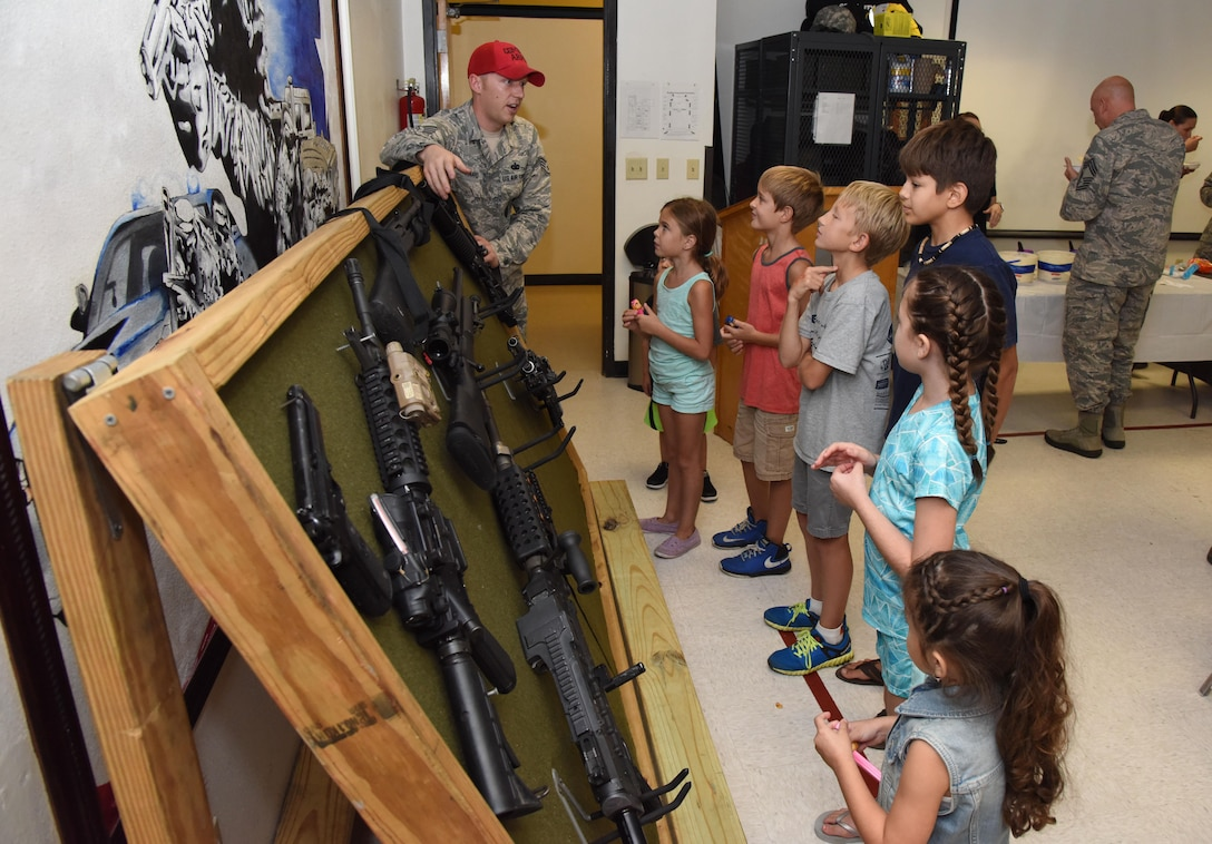Staff Sgt. Jarrod Kinard, 81st Security Forces Squadron combat arms NCO in charge, briefs family members about weapons safety during a family ice cream social at the 81st SFS building July 27, 2017, on Keesler Air Force Base, Miss. The event, hosted by the 81st SFS Defenders Council and Key Spouses, also consisted of a military working dog demonstration and ice cream. (U.S. Air Force photo by Kemberly Groue)