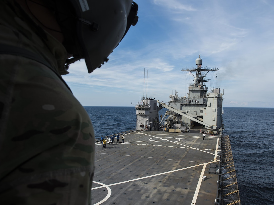 A flight engineer with the 8th Special Operations Squadron watches as his CV-22 Osprey tiltrotor aircraft approaches the amphibious dock landing ship USS Oak Hill (LSD 51) during a deck landing qualification flight off the coast of Virginia, July 25, 2017. Flight engineers are responsible for watching the approach and relaying the approximate distance between his aircraft and the carrier to the pilots, ensuring a safe landing. (U.S. Air Force photo by Airman 1st Class Joseph Pick)