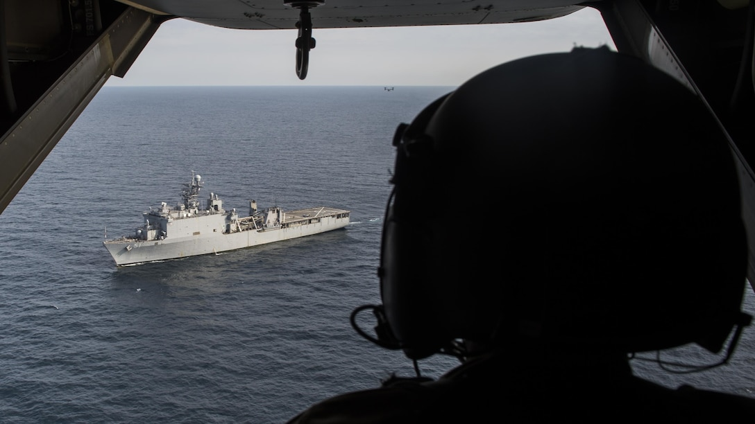 A flight engineer with the 8th Special Operations Squadron looks on as a CV-22 Osprey tiltrotor aircraft departs the amphibious dock landing ship USS Oak Hill (LSD 51) during a deck landing qualification flight off the coast of Virginia, July 25, 2017. Deck landing capabilities allow 8th SOS aircrew to expand the Osprey's global reach. (U.S. Air Force photo by Airman 1st Class Joseph Pick)