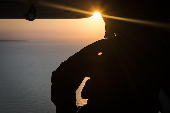 A flight engineer with the 8th Special Operations Squadron scans the horizon during a training mission off the coast of Virginia, July 26, 2017. Flight engineers are responsible for watching the approach and relaying the approximate distance between his aircraft and the carrier to the pilots, ensuring a safe landing. (U.S. Air Force photo by Airman 1st Class Joseph Pick)