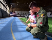 Capt. Jim Henson, a B-1 bomber pilot assigned to the 34th Bomb Squadron, holds his one year-old daughter, Charlotte, after returning from Red Flag 17-3. Red Flag is a joint-exercise that occurs at Nellis Air Force Base, Nevada, and includes air-to-air and air-to-ground scenarios to provide aircrews with a realistic combat environment. (U.S. Air Force photo by Airman 1st Class Randahl J. Jenson)